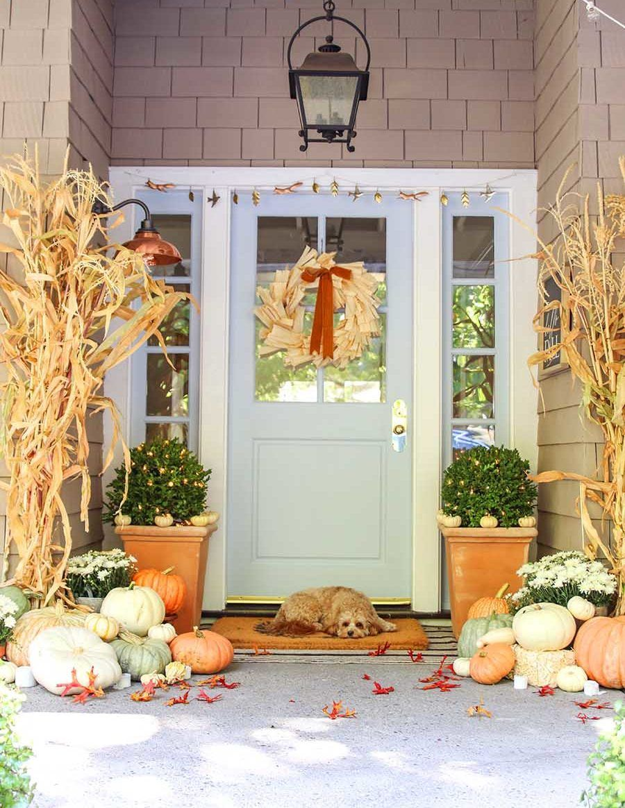 Neutral fall front porch with cornstalks via modern-glam