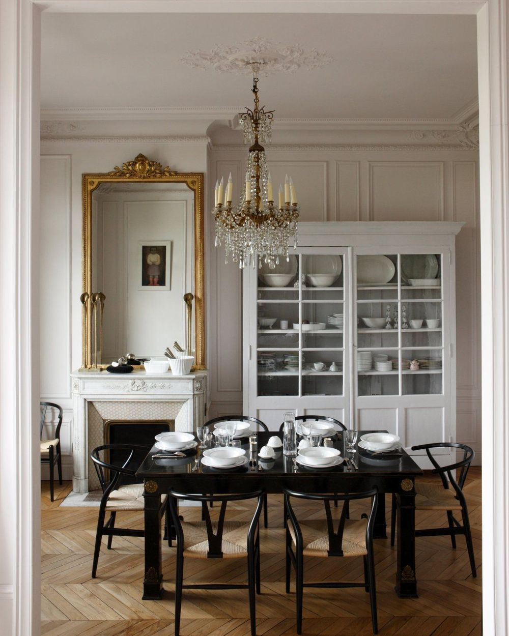 Parisian Dining Room design with Black dining table, Black wishbone chairs and crystal chandelier via Jean-Marc Palisse and CoteMaison