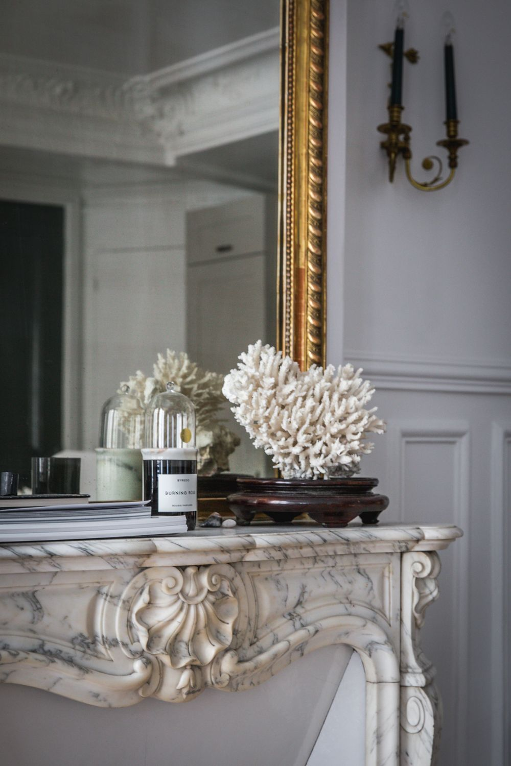 Parisian Fireplace with Byredo candle and coral sculpture via AptLafayetteParis