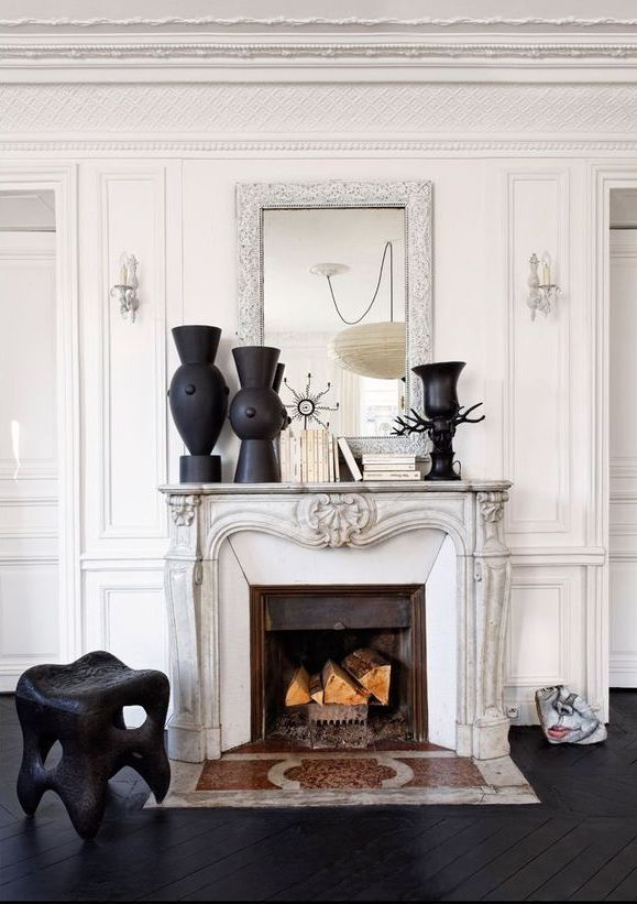 Parisian Black and white Fireplace with Books and black vases via Elle