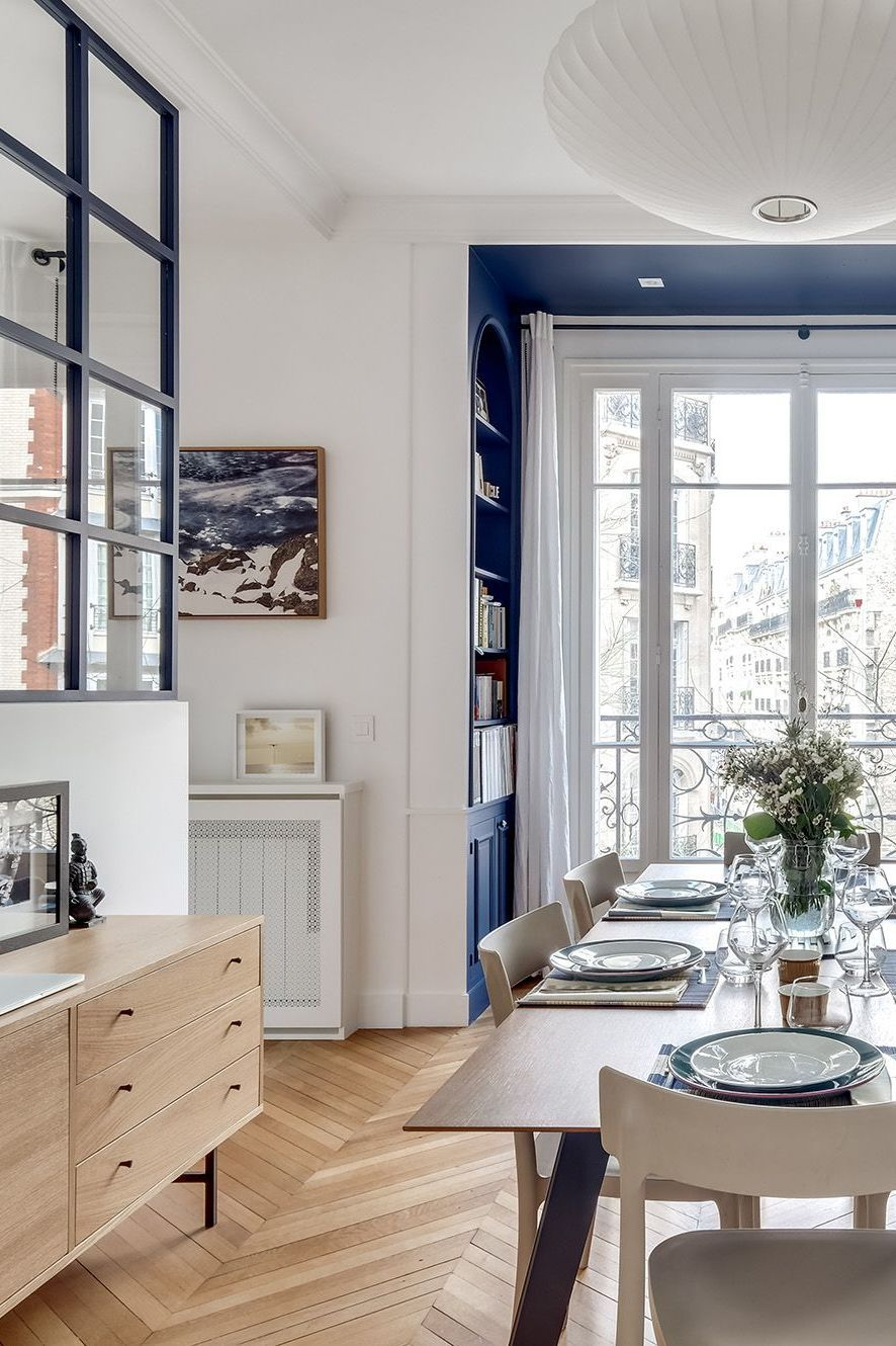 Parisian dining room design with Blue bookshelf and neutral wood buffet via Elodie Cottin CoteMaison