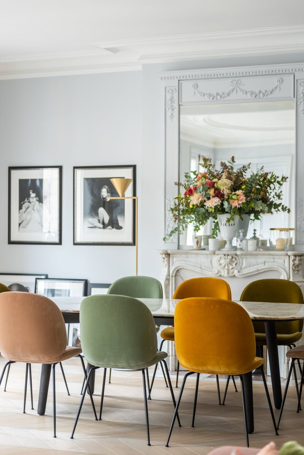 Parisian dining room with yellow, green, and pink dining chairs via The Socialite Family Florence Elkouby