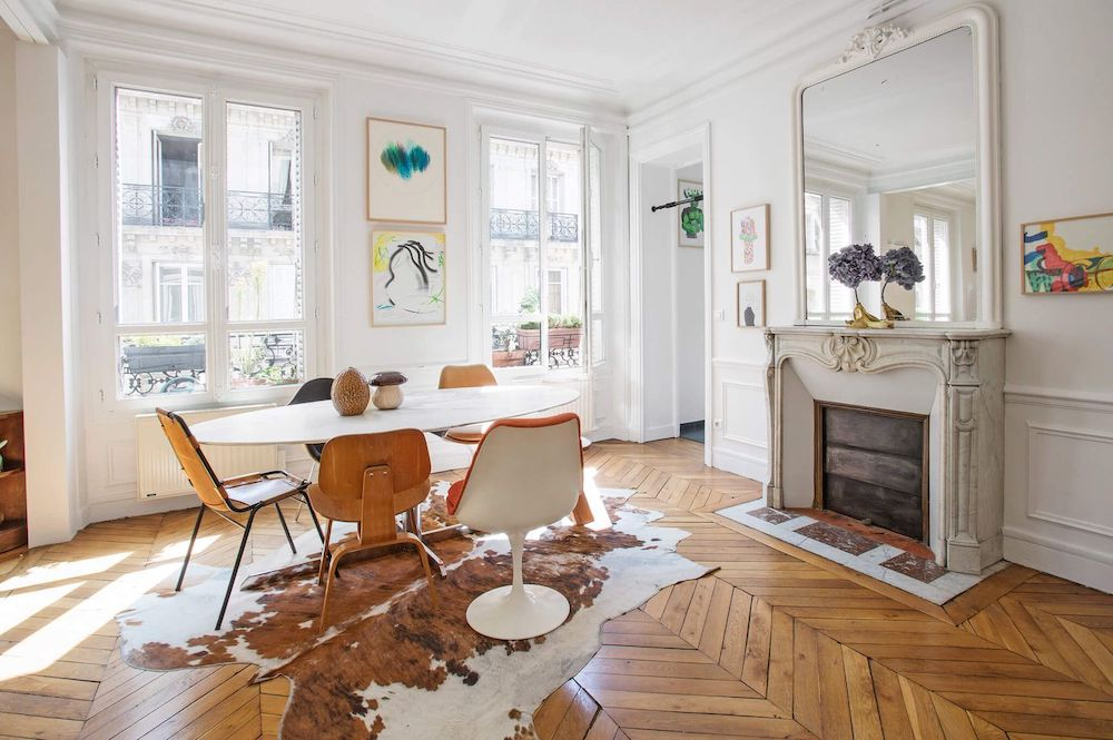 Parisian dining room with Cowhide rug and mismatched dining chairs via Havenin Saint Germain