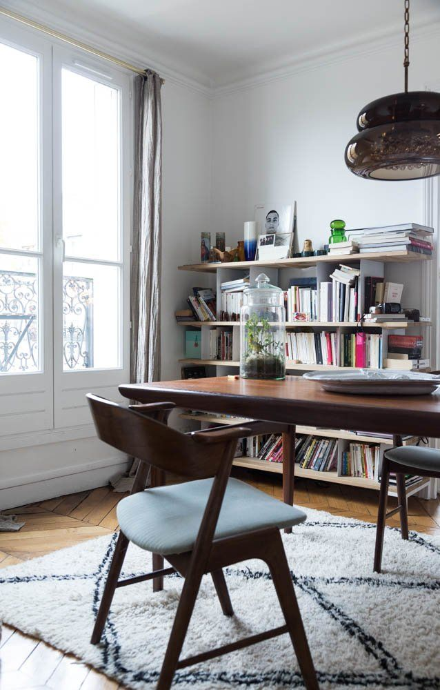 Parisian dining room with brown Mid-century modern chairs and bookshelf via The Socialite Family Sabina Socol