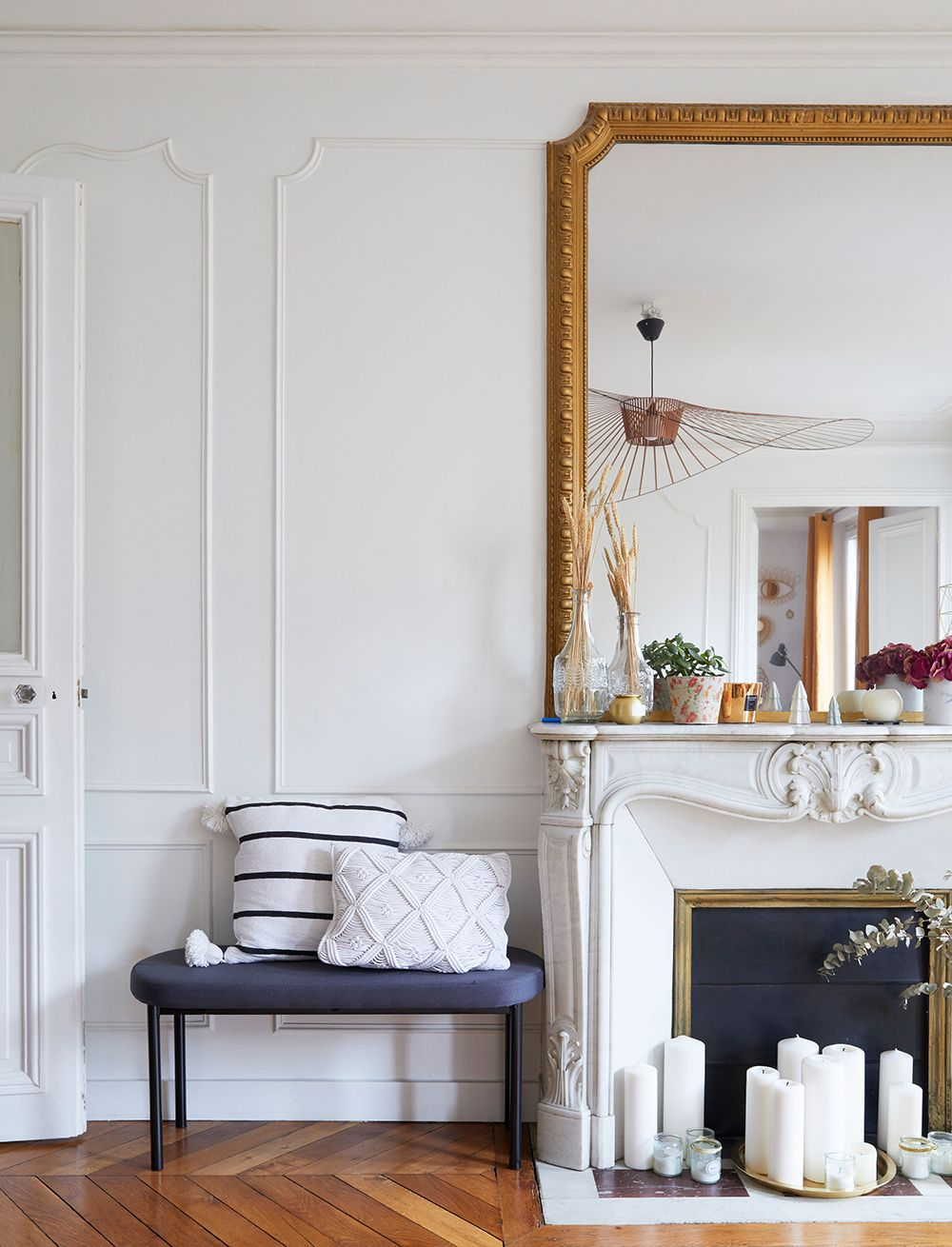 Parisian fireplace decor with White candles in front of opening via Cup of Jo