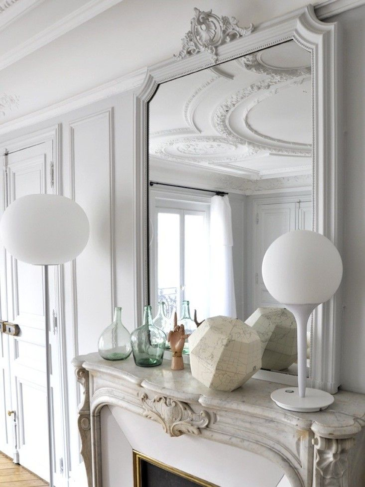 Parisian fireplace with modern white table lamp via Marie-Claire Fresquet