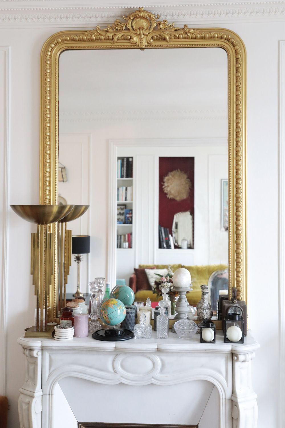 Parisian fireplace with Globe and white vintage fragrance bottles via Hello-hello Camille Omerin