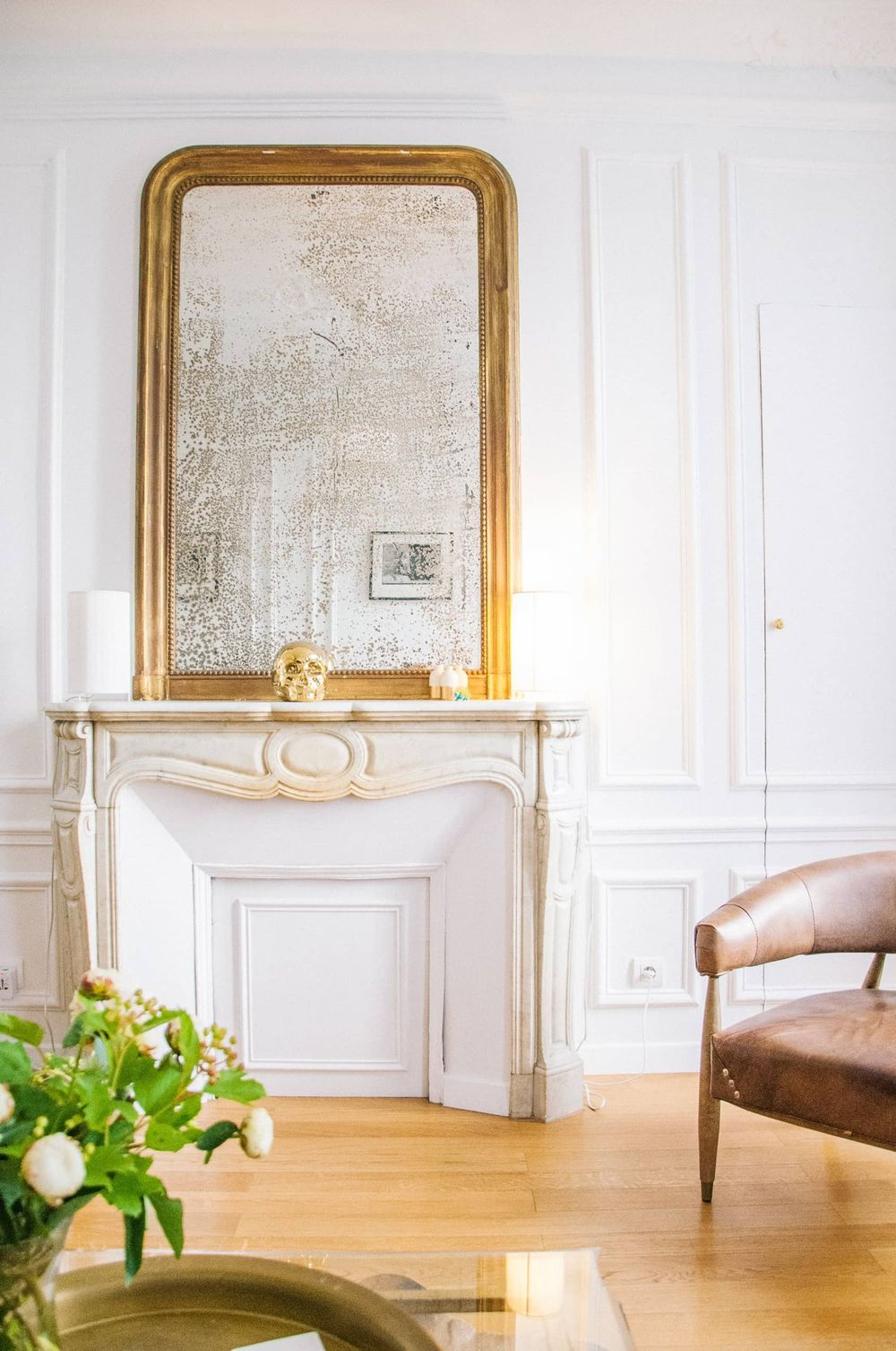 Parisian fireplace with distressed mirror and brown leather chair via Katy Cartland