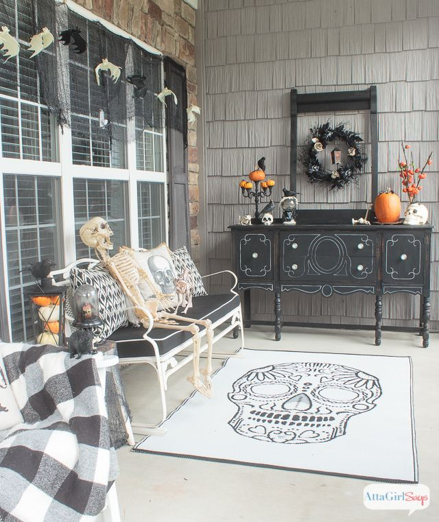 Skull rug on Halloween front porch with skeletons on bench and black cushions