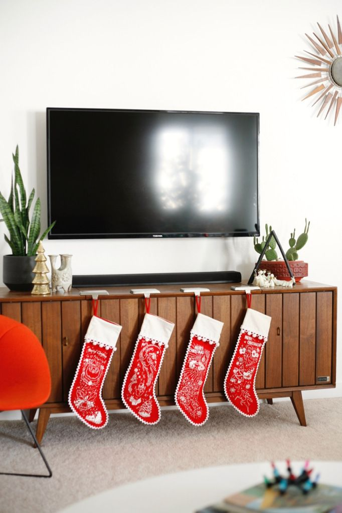 Christmas stockings on a mid-century sideboard via suburbanpop