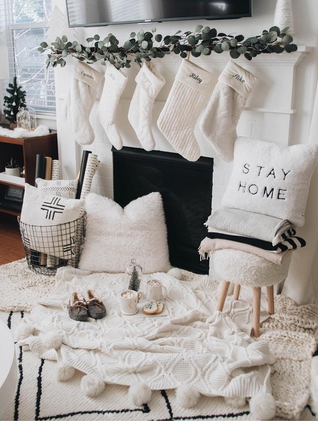 Cozy Winter Home with White Throw Blankets, Slippers, Stockings and a Fireplace via @crystalinmarie