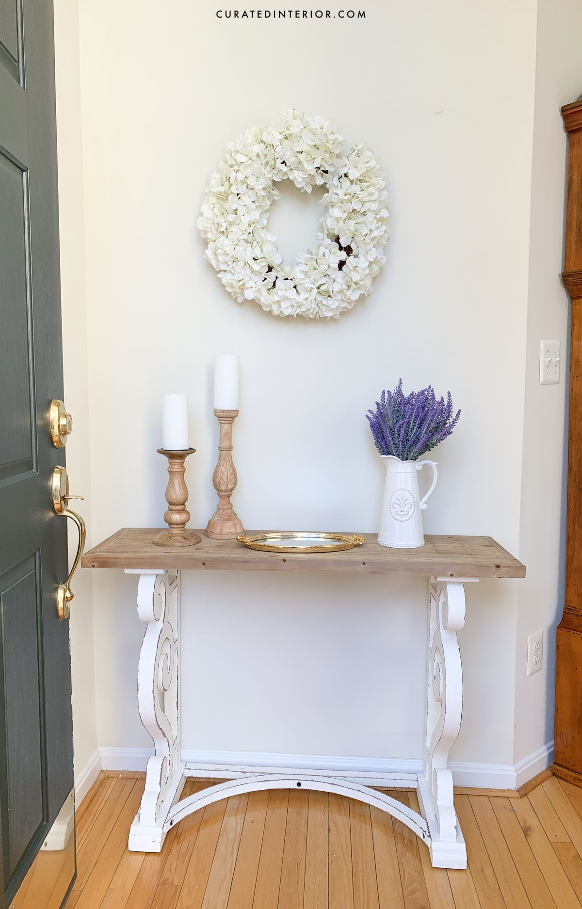 French Country Entryway with Floral Wreath, Wood Console Table and Lavender in a white Farmhouse Pitcher