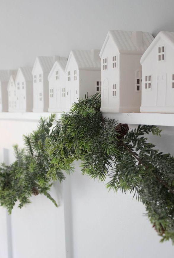 Little white houses on shelf with evergreen via housemixblog