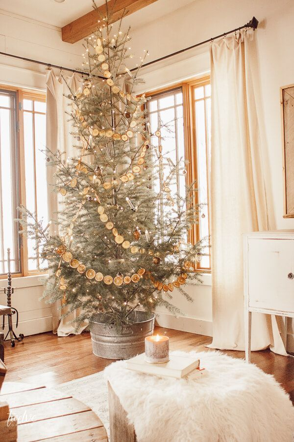 Scandinavian Christmas Living Room with Orange Slice Garland and Faux Fur via twelveonmain