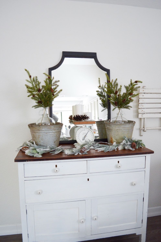 Evergreen stems in galvanized buckets via farmfreshhomestead