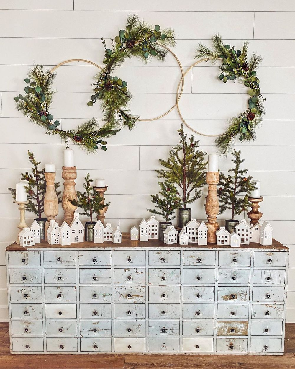 Farmhouse winter console table decor with white houses and evergreen hoops via @cottonstem