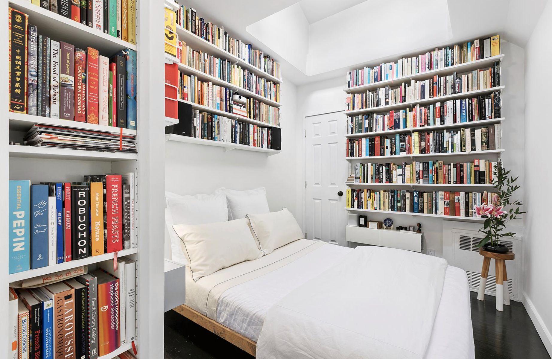 Schlafzimmer mit drei Wänden von Bücherregalen vom Boden bis zur Decke über Apartment Therapy