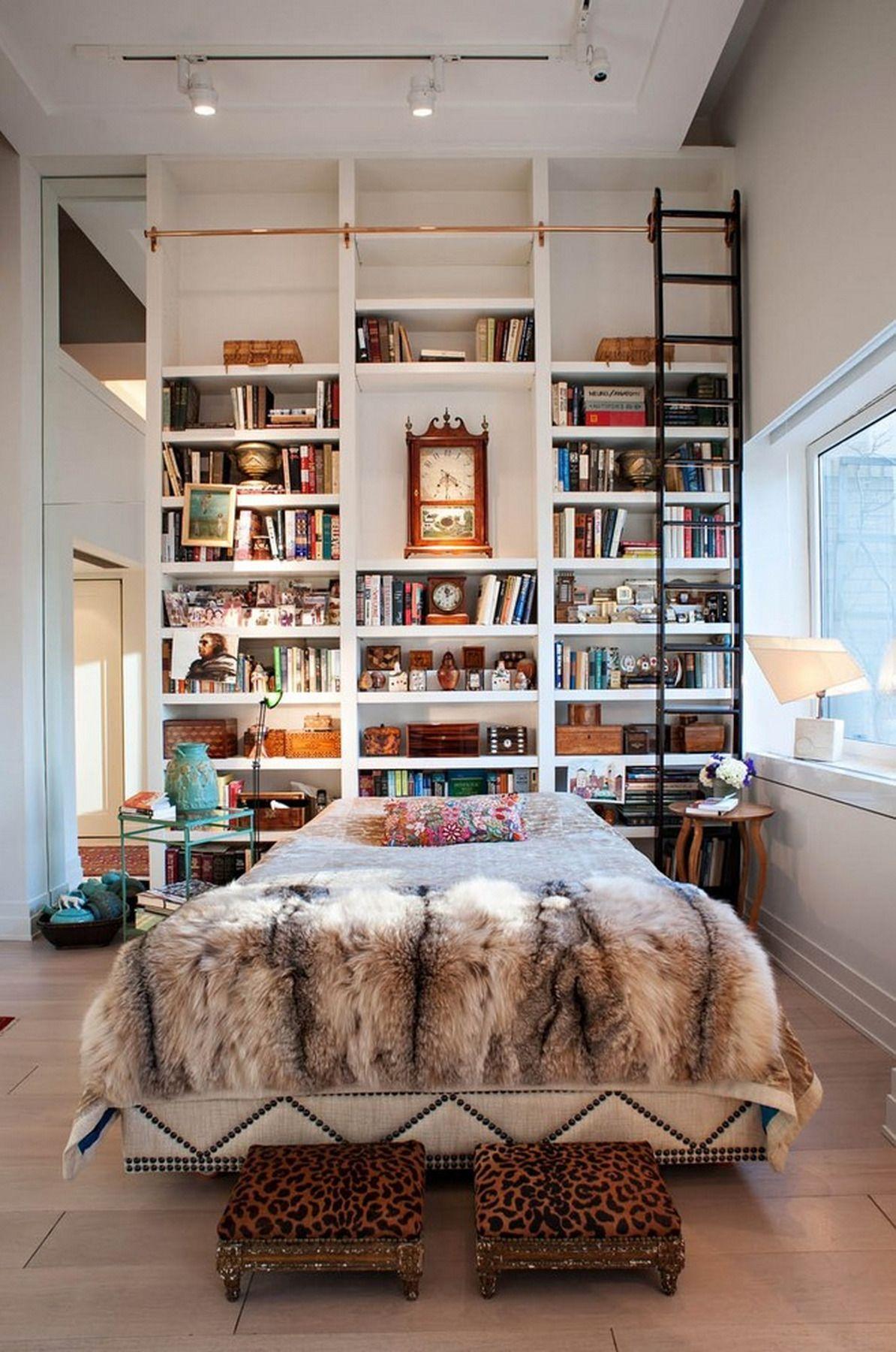 Schlafzimmer mit Schiebeleiter und hohen Bücherregalen