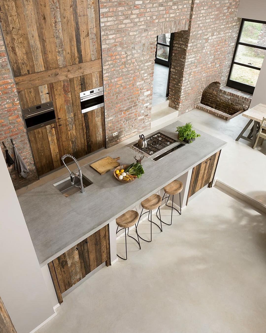 Betonarbeitsplatten in der Industrieküche mit freiliegenden Backsteinmauern und rustikalen Holzplatten via @cavainterieur